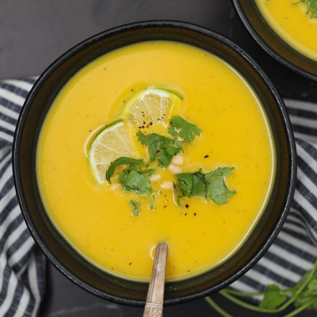 the vegan butternut squash soup coconut milk recipe with garnishes on a black background
